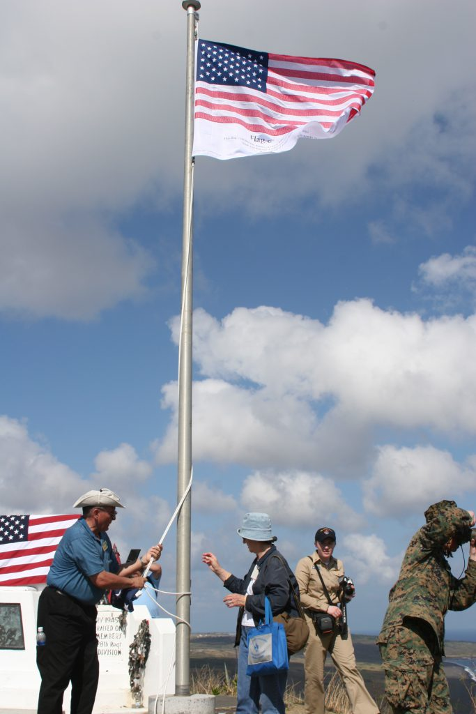 Iwo Jima Tour guests raising flag