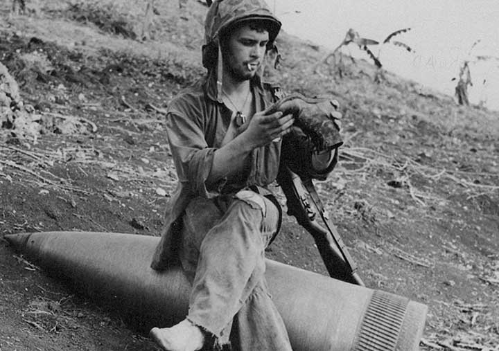 Soldier at Iwo Jima sitting on artillery