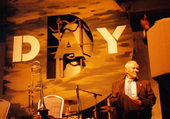 Stephen Ambrose sitting on the stage at D-Day museum